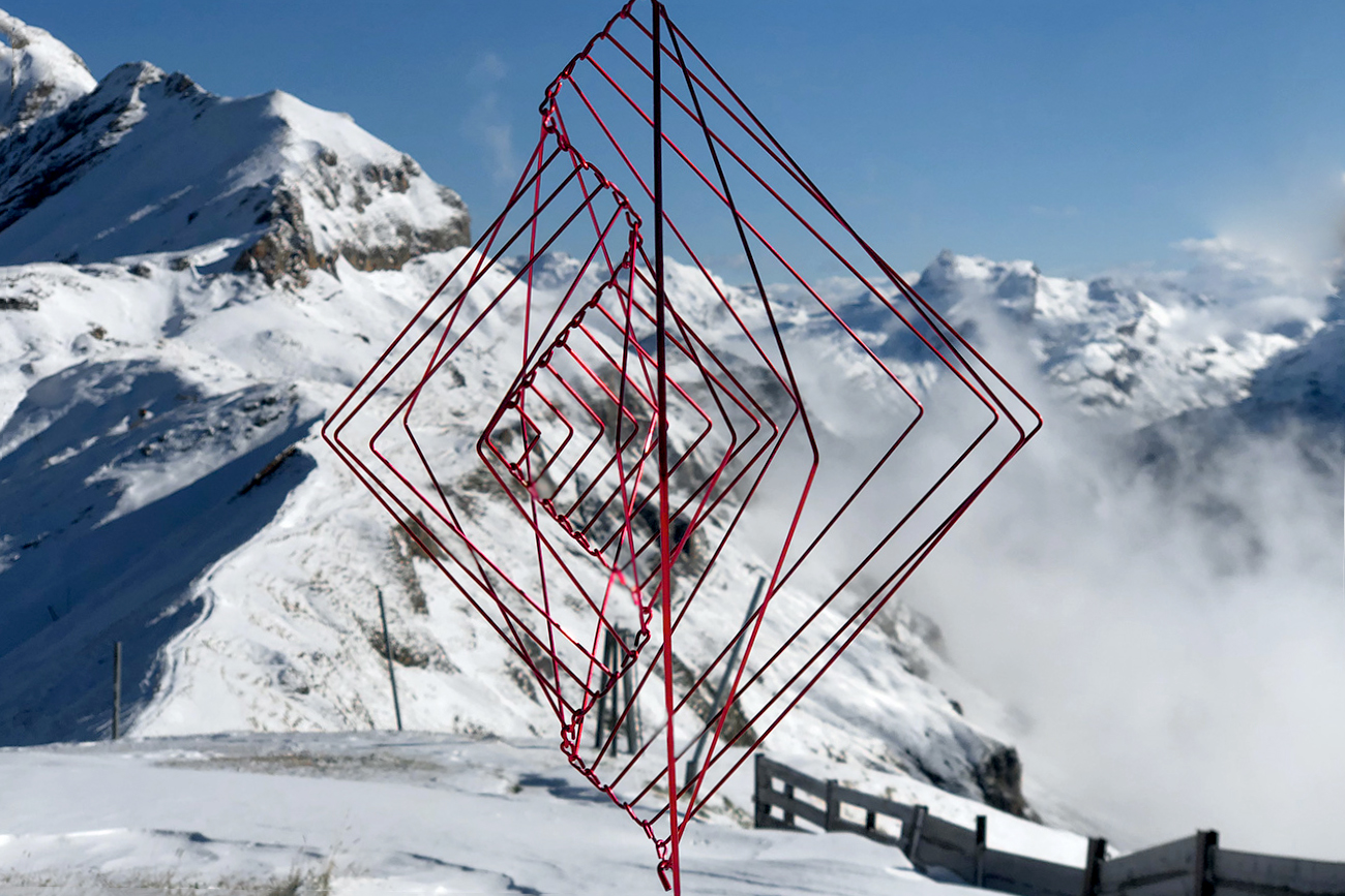 Coral Red Square Wave spinning in the Swiss Alps. A kinetic sculpture made by Ivan Black for Kinetrika