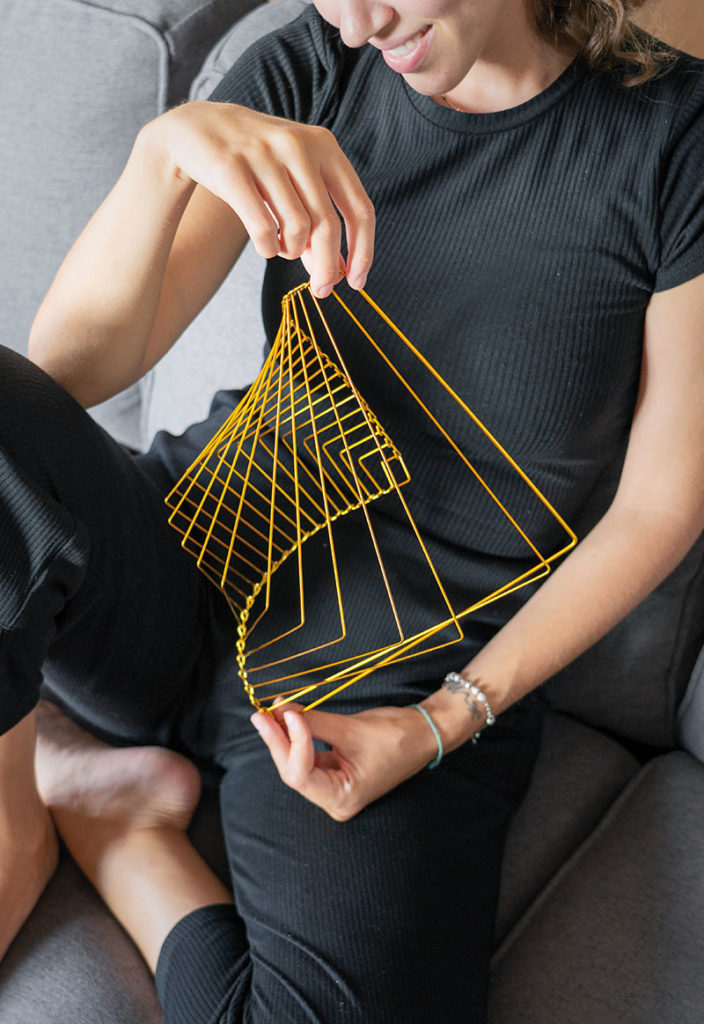 Young woman sitting on sofa, playing on sofa with kinetic toy called Square Wave