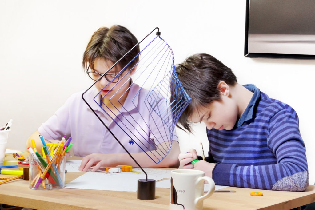 Young twins learning and drawing while relaxing with kinetic toys at home